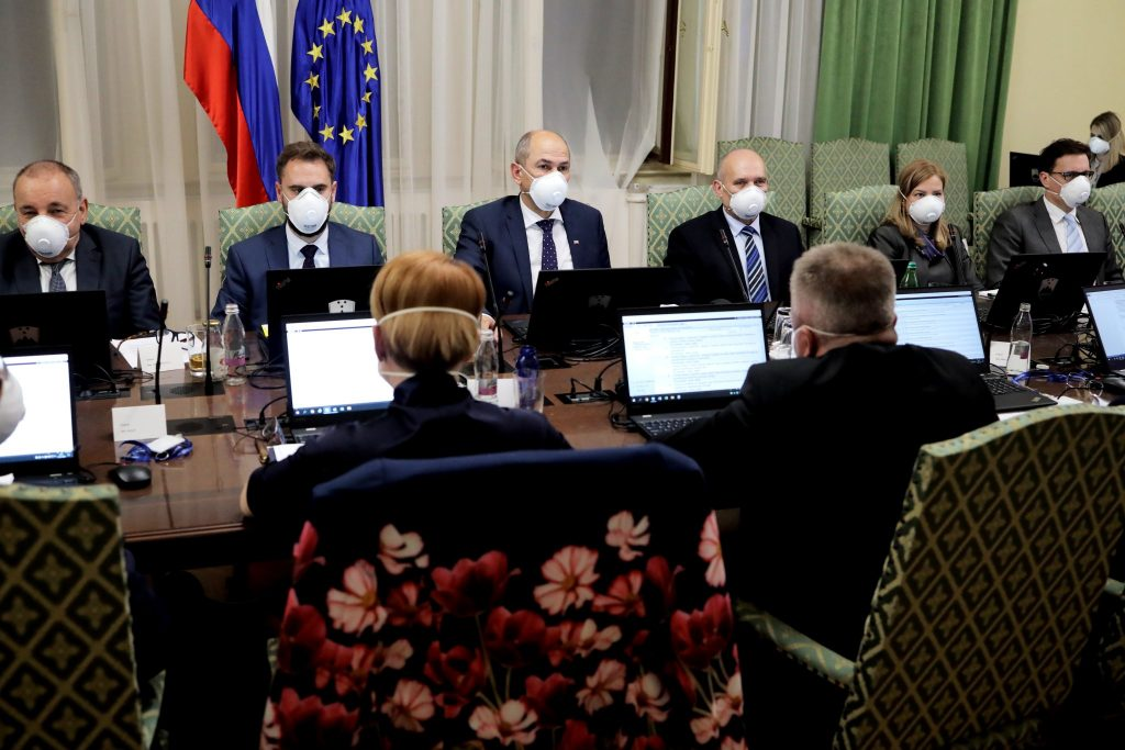 Photo of Slovenian national officials meeting during the corona crisis. All are wearing masks.