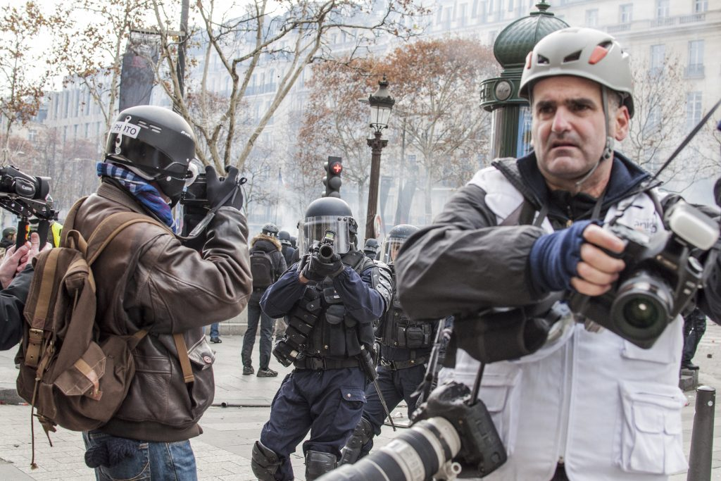 The photo shows journalistts working during yellow vests, while police officers are pointing with a flash ball gun directly towards the viewer.